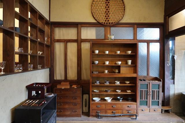 画像: 天井近くには、古道具屋さんで手に入れたという大きなザルが。「壁の空いたスペースになんとなしに飾ってみたんですが、1999年の開店以来、ずっとかけっぱなしです(笑)」と浦田さん