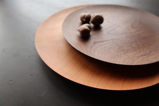 画像: 美しいフォルムが目を引く「丸皿」は、使い勝手も抜群。上がウォールナット、下が桜