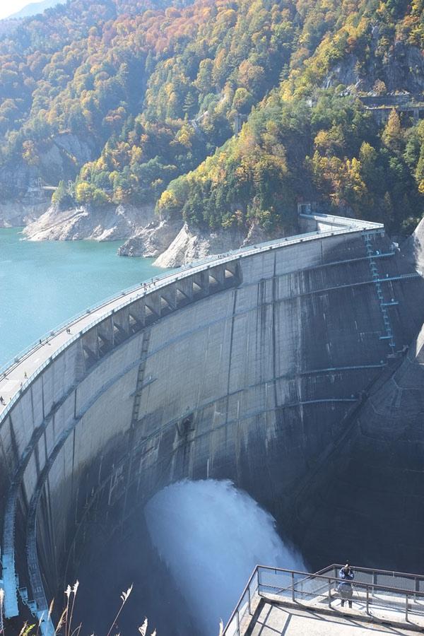 画像: 黒部ダムの放水と紅葉