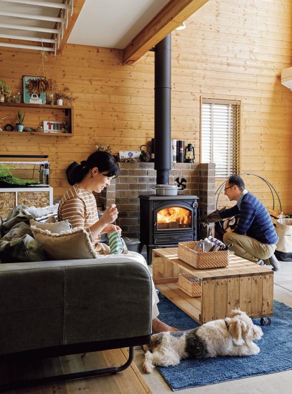 画像: 薪ストーブの火の揺らめきを眺めながら過ごす穏やかな時間。それぞれが好きなことをしたり、コーヒーを飲みながら夫婦でおしゃべりしたり。ワイアーフォックステリアのソラちゃんも、和美さんのそばに寝そべってリラックスしています