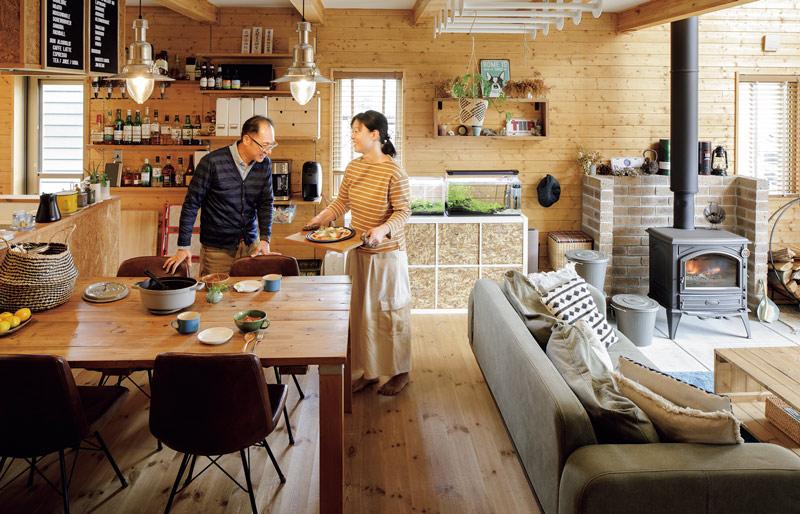 画像: 薪ストーブでピザを焼くと、生地はさくさく、具はジューシーで絶品。天板に鍋を置いて煮込み料理をつくることも。キッチン脇には、優樹さんが好きなウイスキーをはじめ、いろいろなお酒のコレクションが