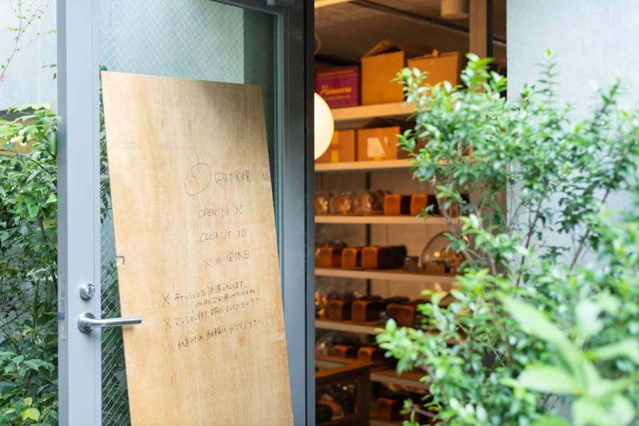 画像: コンクリート打ち放しの壁に、べニア板一枚の手描き看板が味わいを添えています