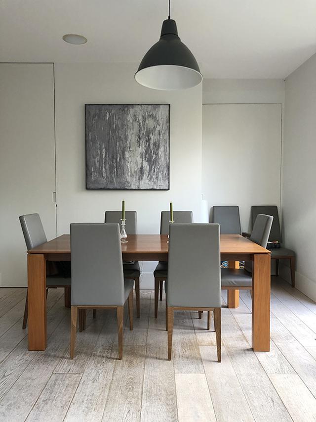 画像: 絵画が飾られたダイニング。絵画と椅子の色がコーディネートされており、印象を引き締めている