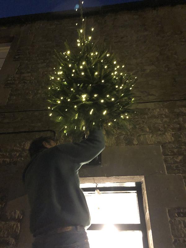 画像: 壁にクリスマスツリーを飾る夫