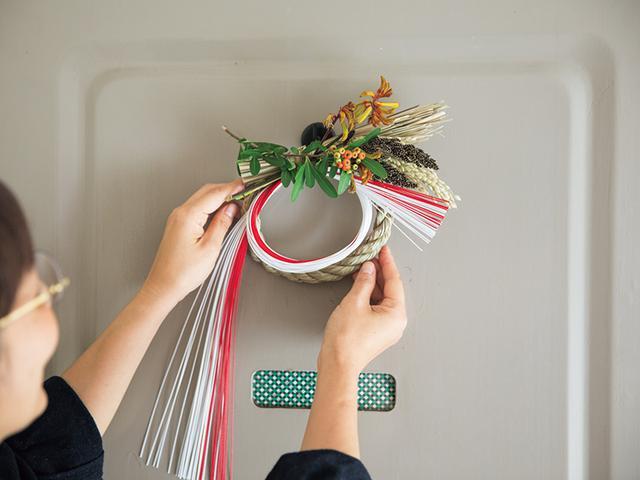 画像: 玄関の扉に飾って。市販のお正月飾りほど主張が強くなく、さりげない存在感。「お花屋さんでその時季に手に入るもので十分だと思います」