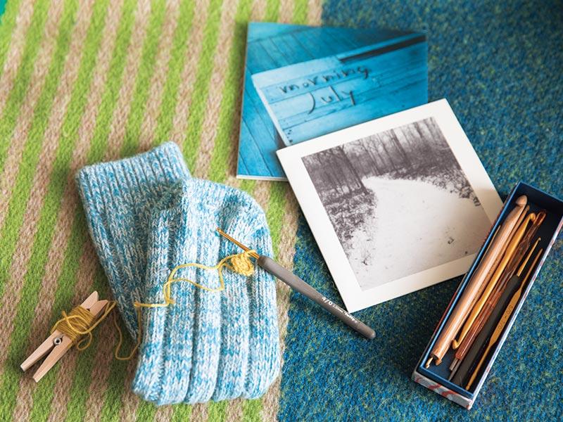 画像: 友人から繕いを頼まれているという靴下。かぎ針でモチーフを編み、穴に付けてポイントにする予定。小さな道具と材料でできるから、移動にも最適