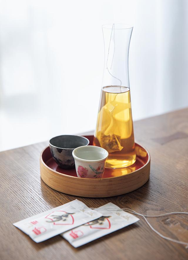 画像: お屠蘇はガラスの酒器に入れ、お猪口は小さなカップで代用。あえてそろいでないのが、いい雰囲気。酒器とカップをのせた丸い小さなお盆は、夫のマツーラさんのおばあさまから譲り受けた