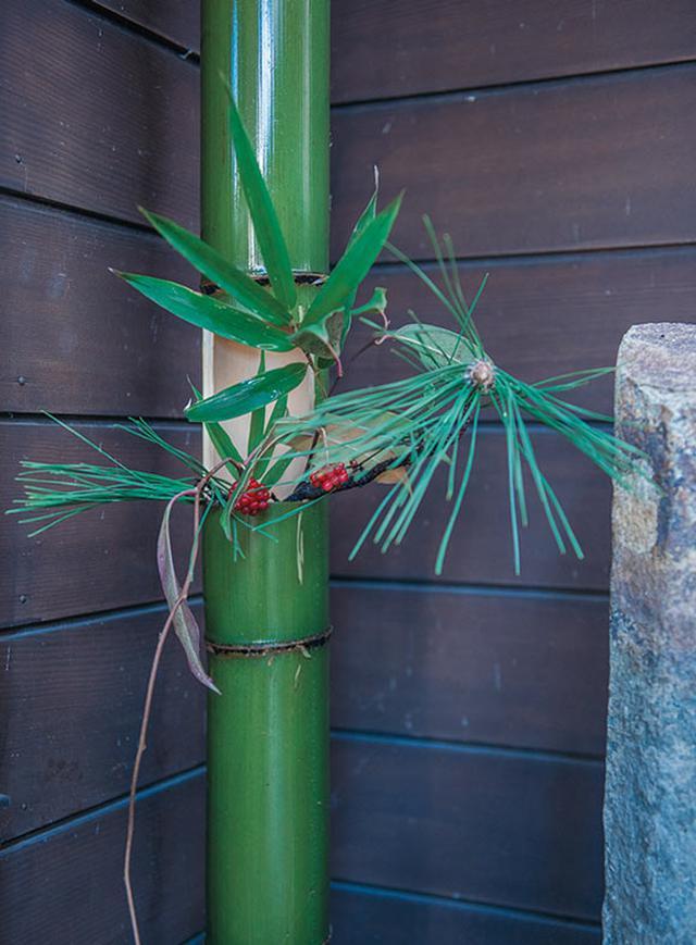 画像: 青竹に菜種油をぬってつやを出し、笹や松、南天を飾って玄関に
