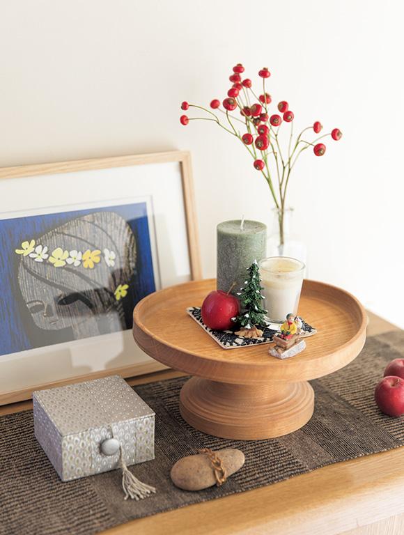 画像: 背の高い赤い実は薔薇の実。木製のケーキスタンドで高低差を出した小さなしつらい。かわいらしいけれど子どもっぽくない。絶妙なさじ加減は、さすがディスプレイのプロ