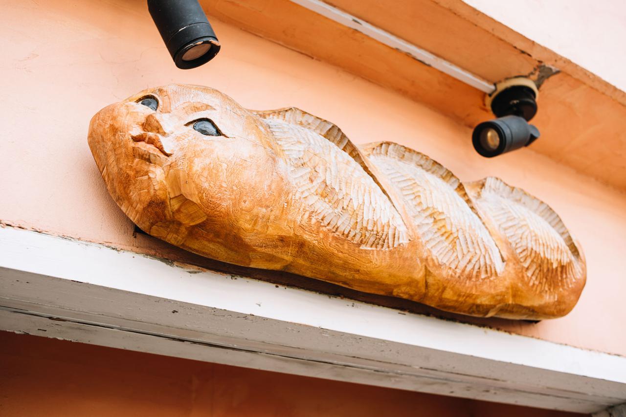 画像: 木彫りのフランスパンがお出迎え。店のシンボルにと、知り合いの木彫り作家さんにお願いしてつくってもらったもの