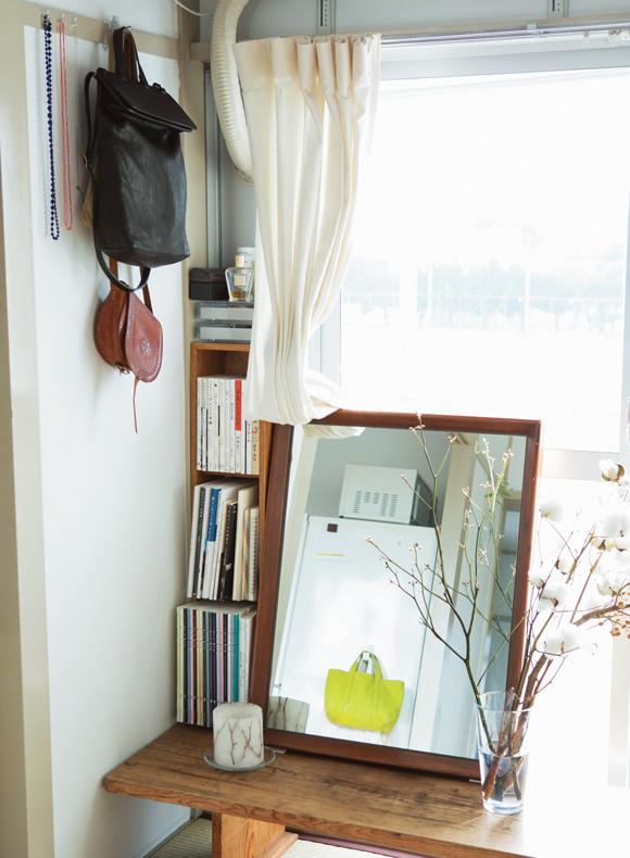 画像: アンティークのベンチテーブルに鏡を置いてドレッサー代わりに。低い家具を配することで空間が広く感じられる