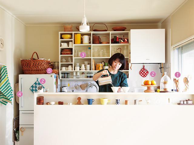 画像: シンクとコンロと平行に配置したキッチンカウンターが、ダイニングスペースとの仕切りに。雑貨類が並ぶオープン棚は「見せる収納」のメインとなるスペース