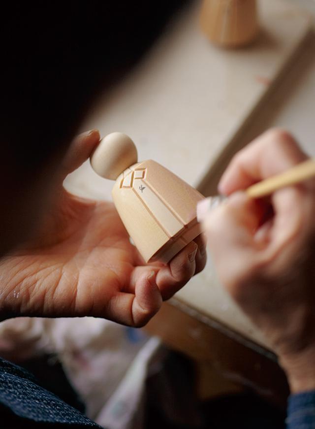 画像: 女雛の後ろ姿。鉛筆で番号がふられているのは、対になる男雛の木目が同じになるために。同じ木からつくられた型に同じ数字が書かれている