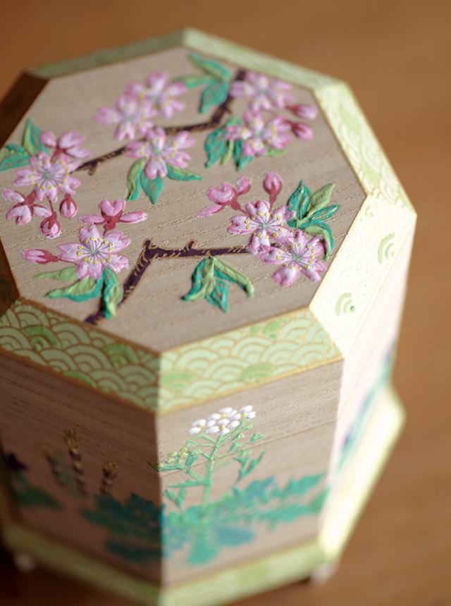 画像: 合わせ貝をしまうための「貝桶」といわれる作品。彩色が難しい桐の箱全体に、桜やなずな、つくしなど春の草花が可憐に描かれている