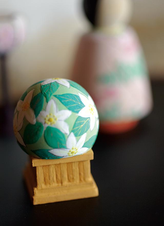 画像: 以前は対のお雛さまのみをつくっていたが、最近は雛道具も少しつくるようになった。雛飾りでつきものの橘の花を描いた飾り。この飾りは平安京の内裏の正面から見て右にあった橘の木に由来するといわれ、左にあった桜の木と対になっている