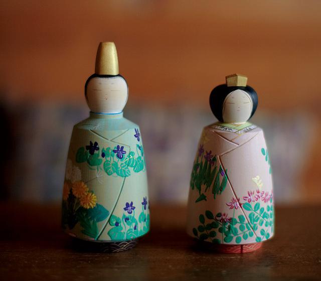 画像: 「彩色雛人形」。木目を生かした薄い彩色が特徴。女雛にはれんげとすみれが、男雛にはすみれとたんぽぽが描かれている。一体は両手のひらに乗るくらいの大きさ。作品は年に数回、行われる個展で入手可能