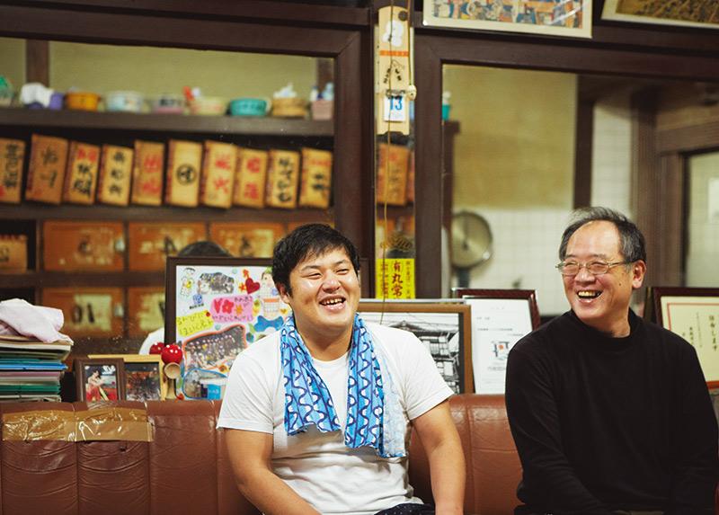 画像: 縁あって「錦湯」2階に住んでいる、落語家の月亭太遊さん(左)。常連の高田さんと、脱衣所の椅子に腰かけて世間話