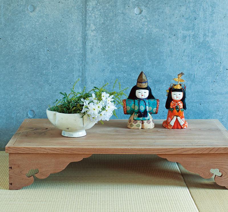 画像: 日本の古道具の台におひな様をのせ、ミモザとリューココリーネを活けて祝いのしつらいに。コンクリートの壁と畳の質感が、あえて新鮮な演出