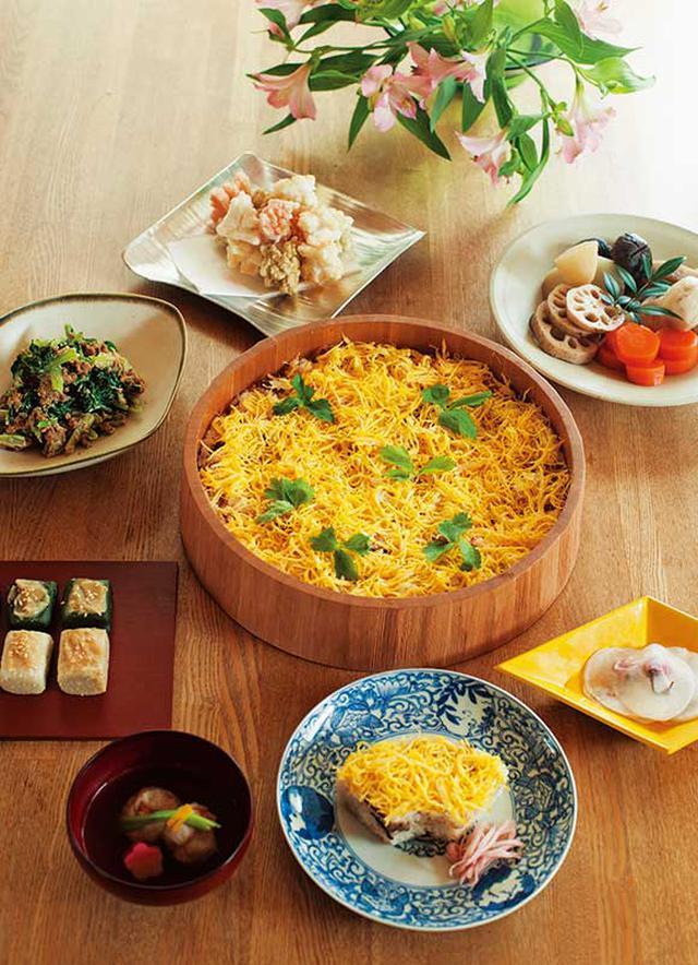 画像: テーブルいっぱいに並んだ、ごちそう。染付や漆など、食器も、お祝いの食卓を意識して選ぶ。娘さん用のちらし寿司は、松の型抜きを使って特別感を