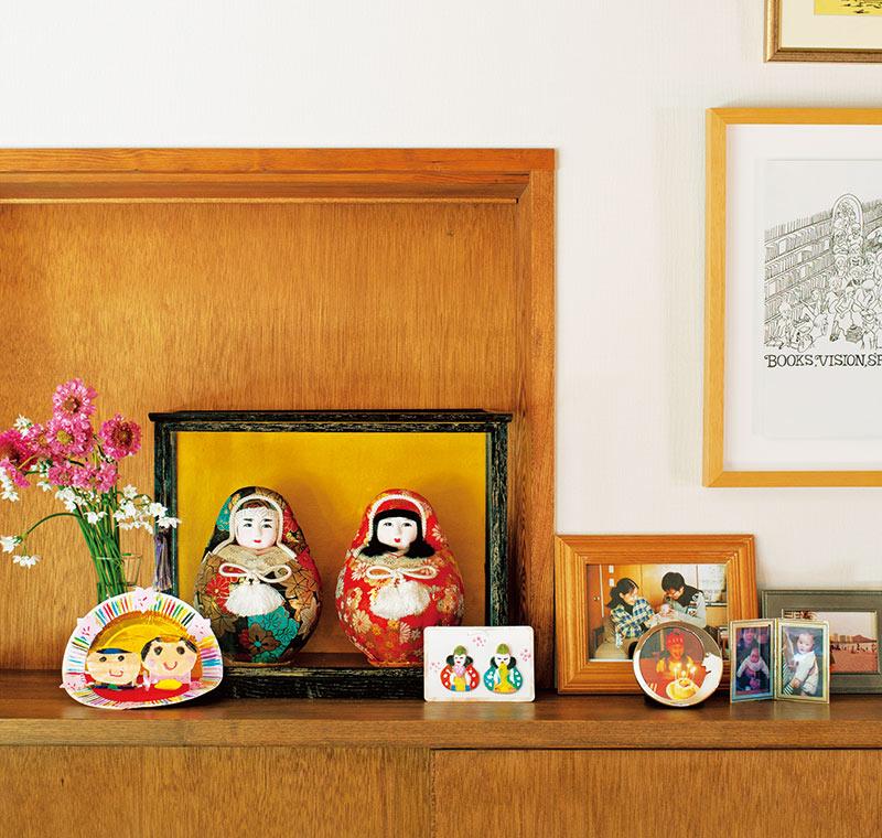 画像: キッチンとダイニングをつなぐカウンターが、だるまびなの定位置。たくさんの写真立てやご主人が描いたイラストにも、すっとなじんでいる