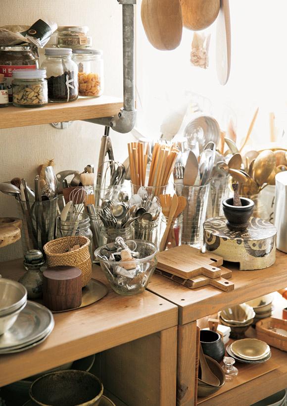 画像: 食器棚には、ジャム瓶やグラスを利用して、カトラリーやへら、トング、菜箸などの道具を収納。小分けができて使い勝手がいいほか、統一感も出て、見た目もすっきり