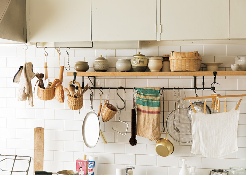 画像: 一番左、コンロの上に吊るしているのは鍋つかみ。その隣から右に向かっては、主にシンクで使う道具。野菜ブラシやタワシ類、ふきんかけ、手ふき用クロスなど。どれも、必要なときにすぐ手に取れる位置にある