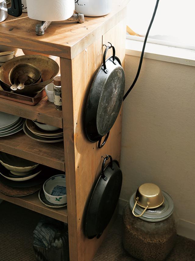 画像: 食器棚の側面もくまなく活用。フックを取り付けて、高さのないパエリア用の鉄鍋を、ふたつ上下に吊るしている。コンロに立って振り向けば、すぐ手が届く場所で、便利