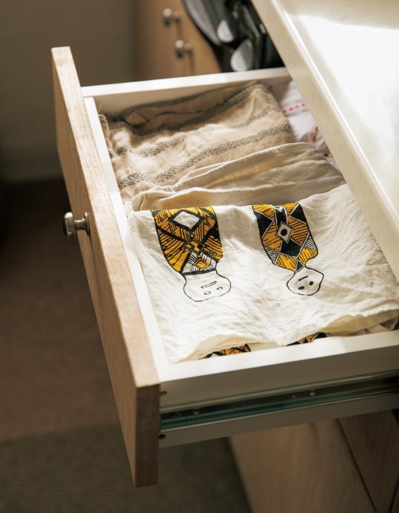 画像: たくさん持っているキッチンクロスは、まずは吊り下げたざるに収納。完全に乾いたら引き出しに入れ、ローテーションで使用