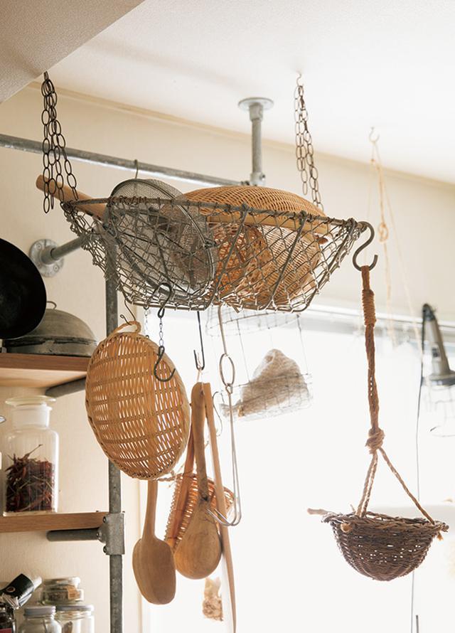 画像: 使ったのは、仕事で譲り受けた店の什器用のかご。チェーンとフックで天井に取り付け、ざるの収納場所に。さらに、網目にフックをひっかけ、木べらや、ゆでもの用のかごなども吊るしている