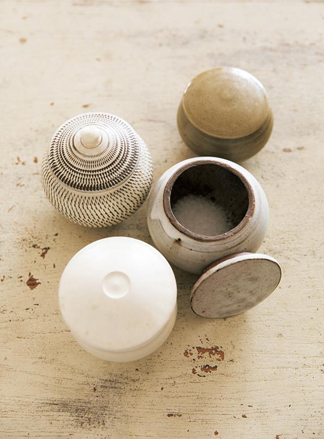 画像: フランスや沖縄のものなど、料理によって使い分ける塩と、少しずつ自分で集めた塩壺。小鹿田焼や出西窯のものなどがある