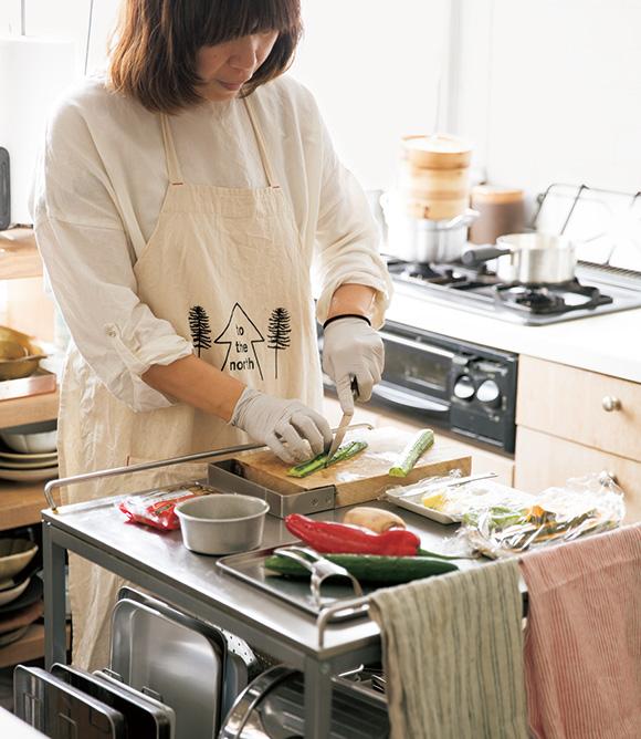画像: ボウルやバット類を収納しているイケアのワゴンは、調理台としても活躍。バーにはクロスをかけて