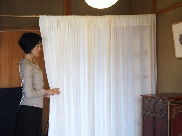 画像: 玄関ホールでは、竹竿に通した綿布をパーティションに。ほんのり向こう側が透けるので、空間が重くなりません
