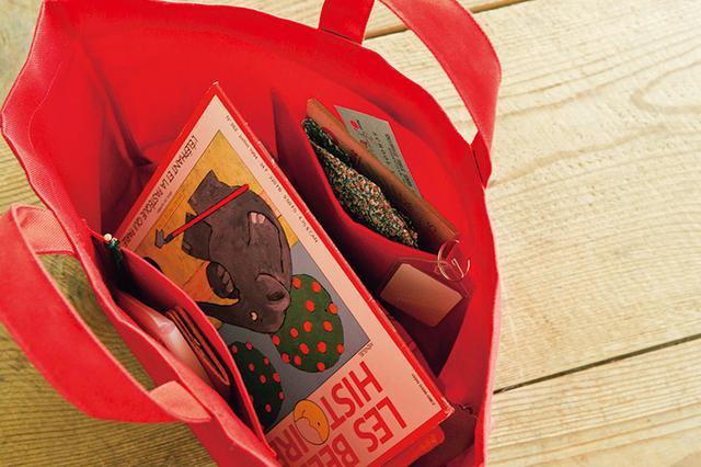 画像: 名札を下げられるタブは、入れ口の折り返しに挟む仕立て。広いマチと両内側に付けたパッチポケットで、たっぷりと物が入る