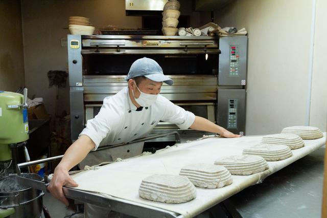 画像: 大きなオーブン板をひとりで抱える清水さん。効率重視のドイツのパンづくりを叩きこまれただけあって、驚きの量をひとりで焼き上げていきます