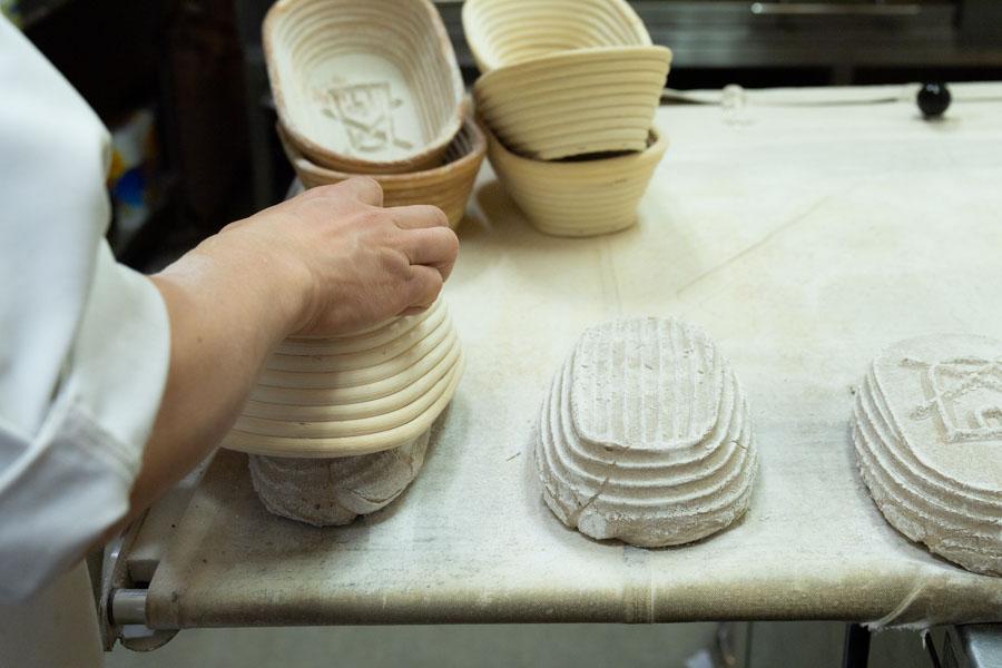 画像: カゴから「ロゲンブロート」の生地を取り出しているところ。カゴの凹凸が、パンの模様になるんですね!