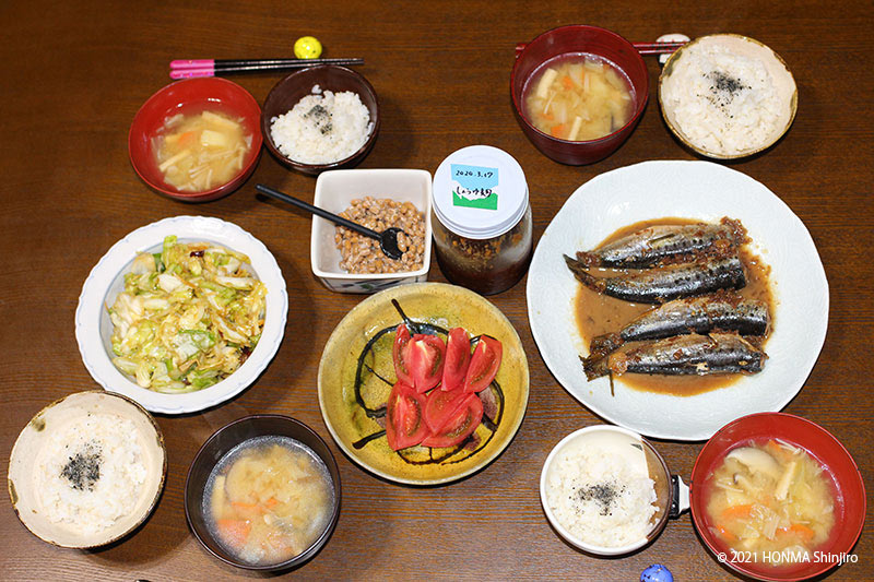 画像: 本間さん家族のある日の夕食。この日は、味噌汁と雑穀ごはん、イワシの梅煮、キャベツのしょう油漬け、トマト、しょう油麹で食べる納豆