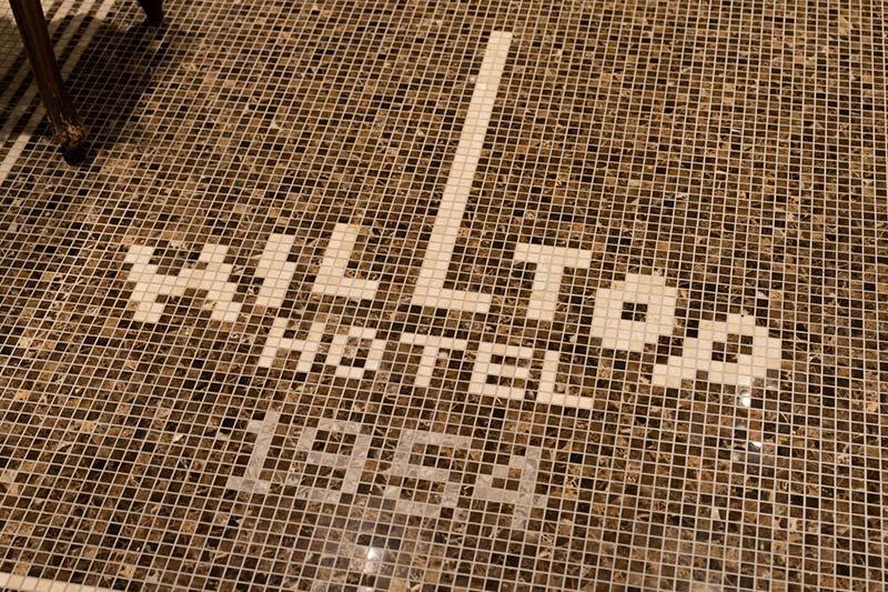 画像: 珍しいタイルの床面にホテルのロゴのあしらい
