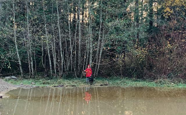 画像: 所有する敷地は15エイカーほど。昨夏に掘った池のほとりに佇むUAさんの長女と愛犬タワ