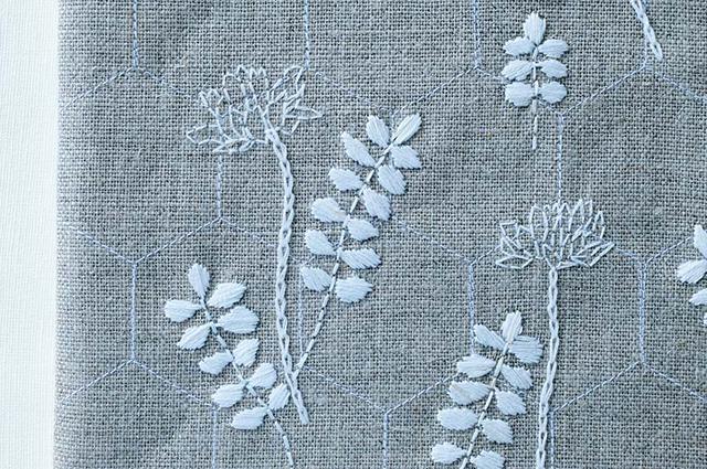 画像: 「レンゲ」。麻の布にミシンで蜂の巣をイメージした六角形をステッチし、その上に白の刺しゅう糸でレンゲの花を刺して、バッグに仕立てた