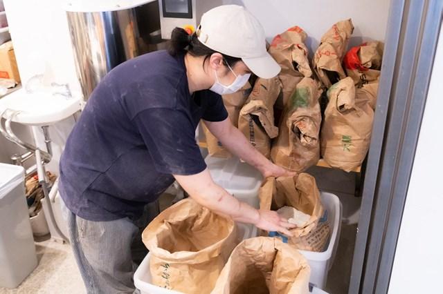 画像: 厨房には小麦粉の入った袋がたくさん!「何種類あるか、自分でも把握してなくて」と原さん