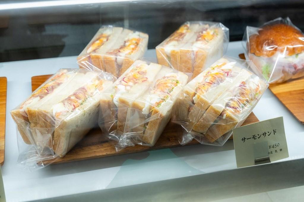画像: 具材たっぷりの「サーモンサンド」など、お昼時にはサンドイッチ類が充実