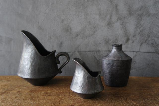画像: 炭化焼成でつくられた「炭化花器」は、光沢を持ち、鉄のような風合い。「実物を目にしたお客さまからも、『金属ですか?』と聞かれるほどです」と小笹さん