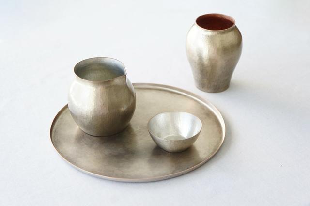 画像: 新潟県の伝統工芸、鎚起銅器の作品。手前が盆、片口、猪口、奥は一輪挿し。鎚起銅器は経年変化が楽しめ、使うほどに色に深みが増します
