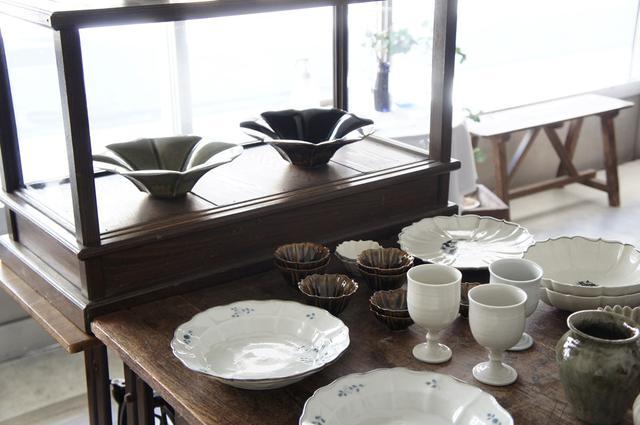 画像: 手前の染付は志村和晃さん、奥の花型の鉢は宮田竜司さんの作品。棚やテーブルは、お隣の新発田市にある古道具屋さん「古道具ハチミツ」で揃えたものが多いそう