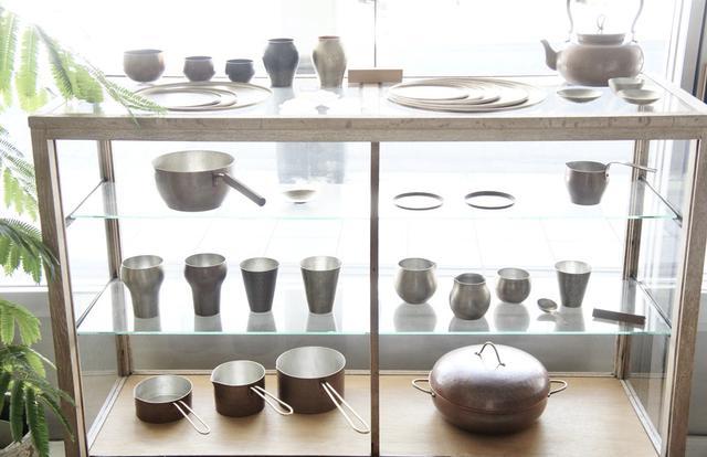 画像: 大橋保隆さんが手がけた、鎚起(ついき)銅器の食器や調理器具も並びます