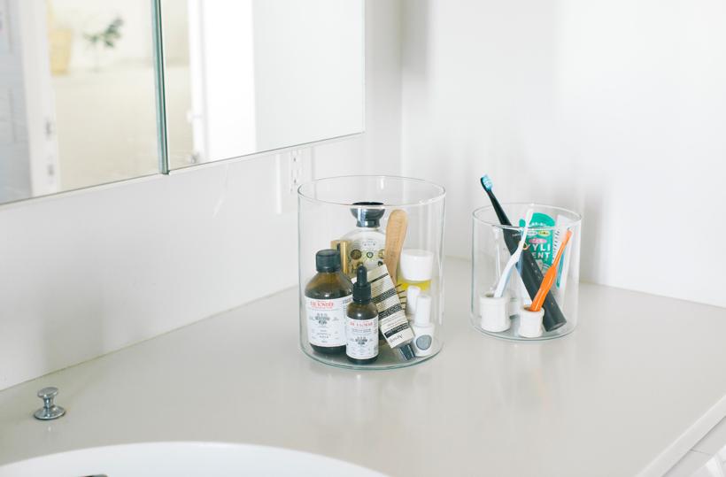 画像: 左)背の高い化粧品のボトルやブラシを入れたガラス容器の大きさは、直径18×高さ20cm。 右)先ほど文房具を入れていた容器(直径14×高さ15cm)には、歯ブラシや歯磨きを。