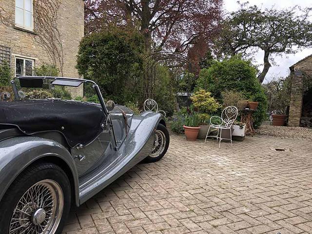 画像: クラシックカーが置かれた前庭には、古いシンクを利用した植木鉢が置かれています
