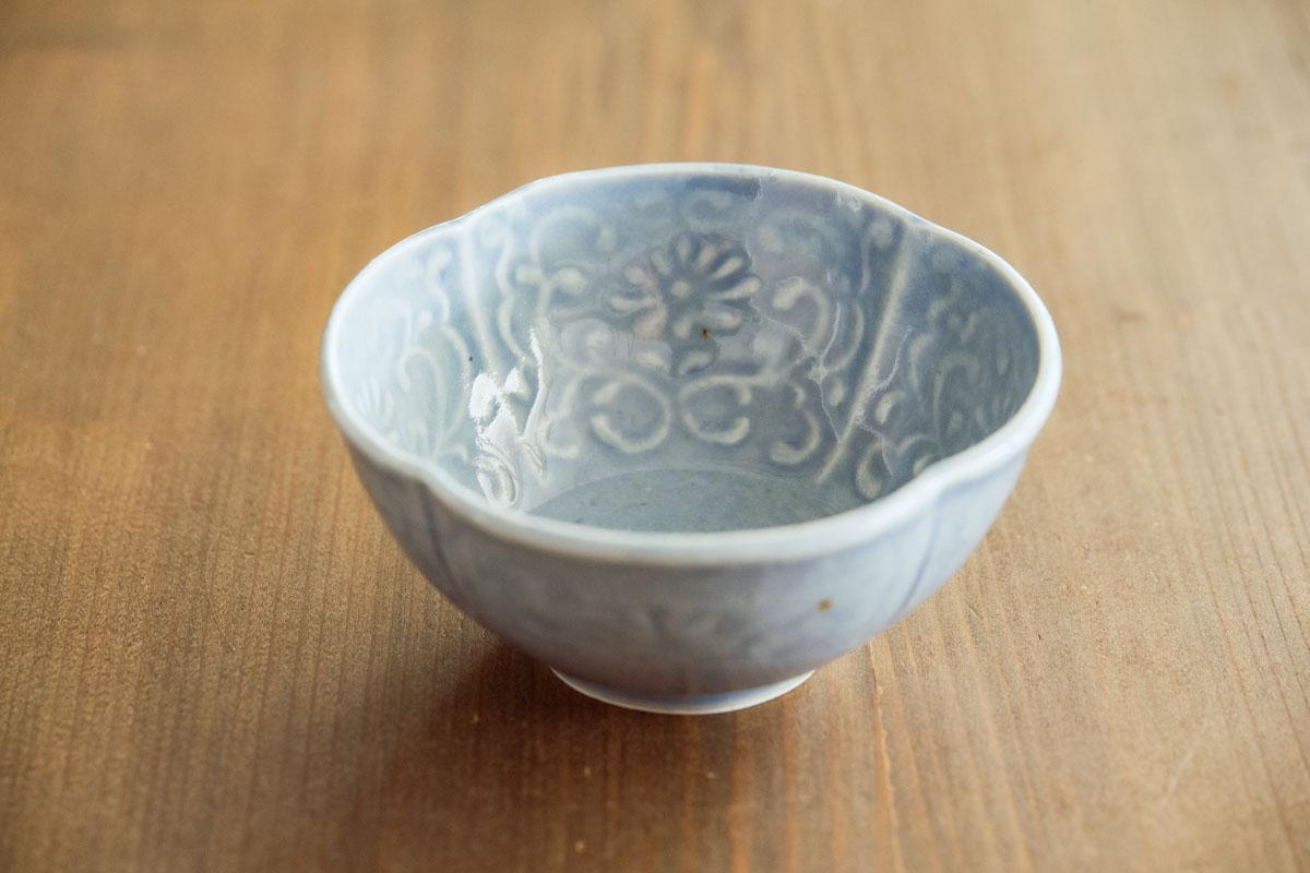 画像: 佐藤もも子さんといえば染付ですが、ほかに瑠璃釉や白磁も手がけ、ごく最近では色絵にも挑戦されているのだとか。写真は「淡瑠璃陽刻文木瓜小鉢」