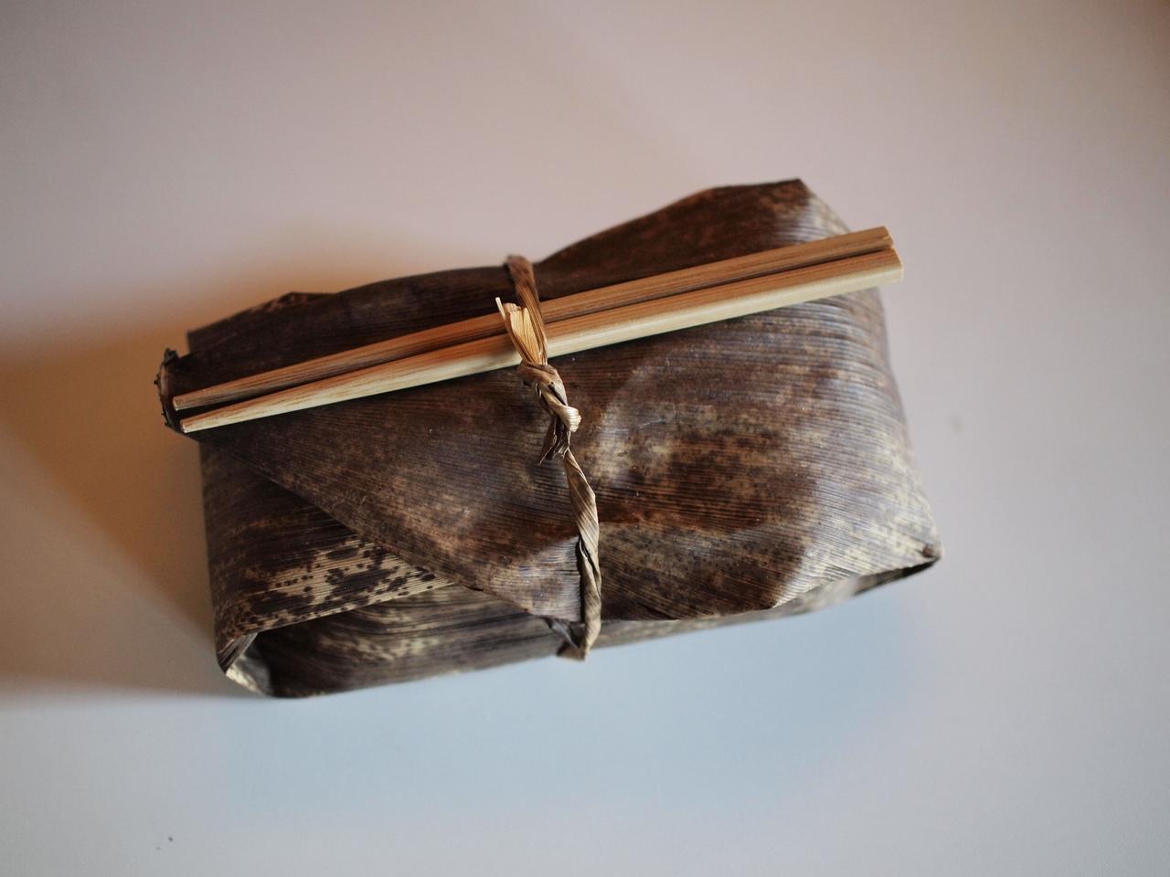 画像: 包む紐も竹皮の端を手で割いてねじったものを使います。竹箸もお弁当サイズに合わせて短く切って、持っていきやすくしました。食べ終わった後は水洗いして干しておけば繰り返し使えます