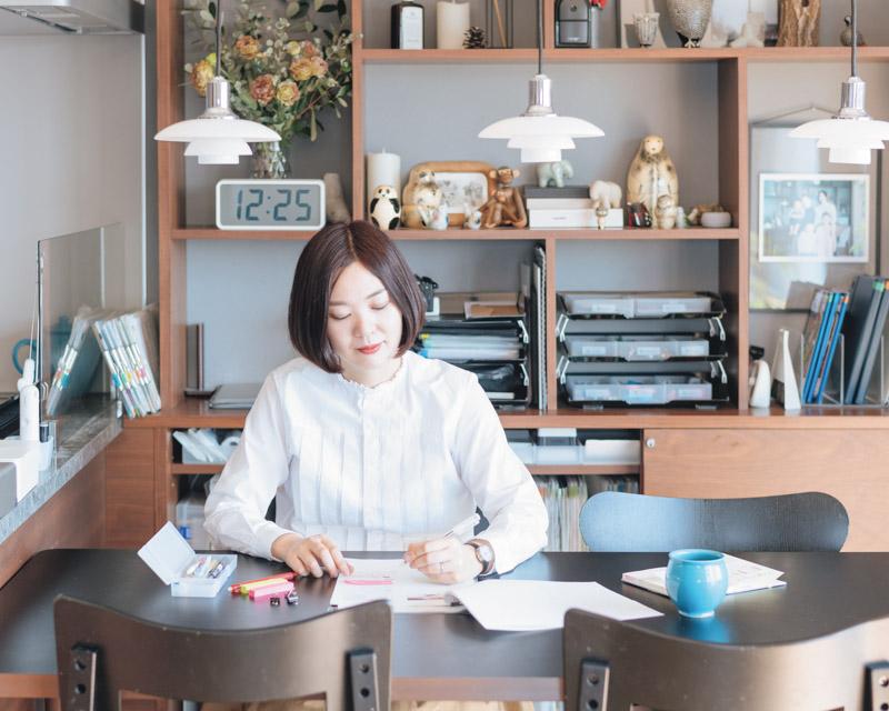 画像: 飾り棚の前が私の定位置。テーブルをリセットしやすいよう、すぐ後ろに仕事道具や書類の収納場所を設けました